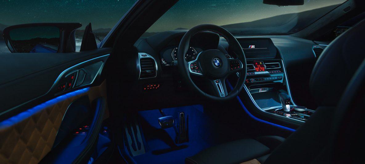 BMW M8 Competition Coupé, Interieur bei Nacht mit M Lederlenkrad und blauem ambienten Licht bei geöffneter Fahrertür.